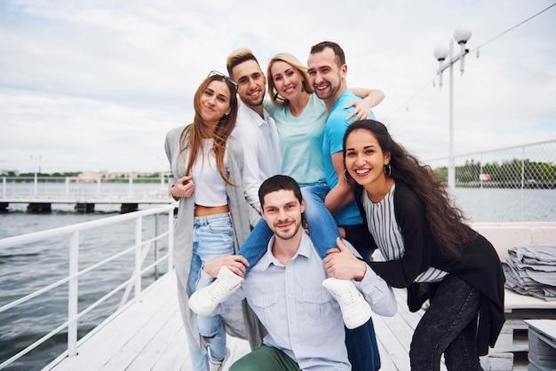 Portret van een jonge en gelukkige mensen in rust op de pier. vrienden die genieten van een spel op het meer. positieve emoties. Gratis Foto