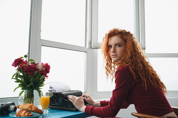 Portret van een jonge ernstige roodharige vrouw te typen Gratis Foto