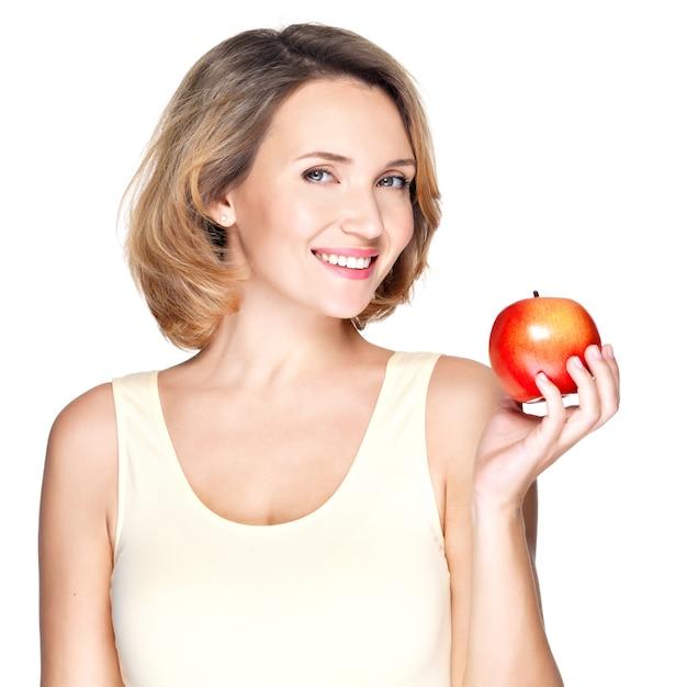 Portret van een jonge glimlachende gezonde vrouw met rode appel - die op wit wordt geïsoleerd. Gratis Foto