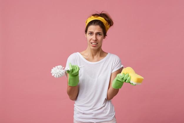 Portret van een jonge huisvrouw die een wit t-shirt, groene handschoenen en een gele sjaal op het hoofd draagt met borstel en spons met fronsend gezicht dat niet wil schoonmaken Gratis Foto
