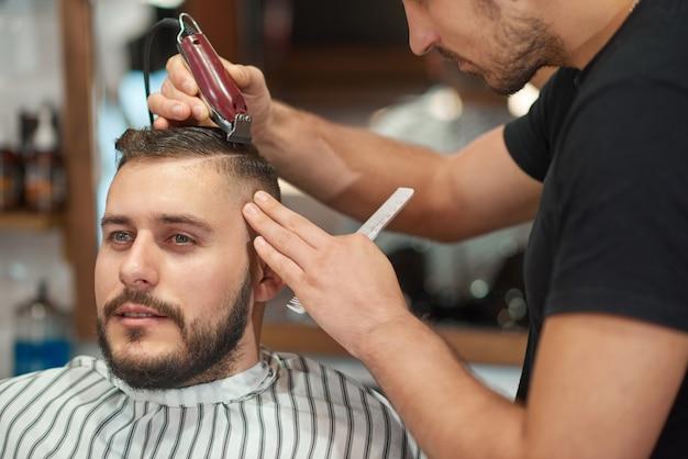 Portret van een jonge knappe man die geniet van het krijgen van een nieuw kapsel bij de kapperszaak. Gratis Foto