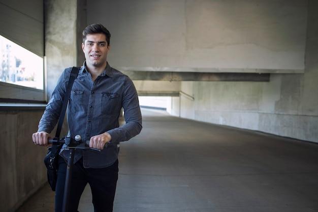 Portret van een jonge knappe man met schoudertas staande op zijn elektrische scooter Gratis Foto