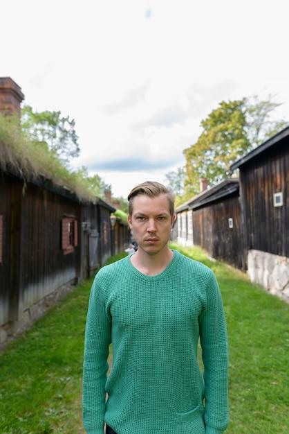 Portret van een jonge knappe scandinavische man in het midden van uitgelijnde oude houten huisjes Premium Foto