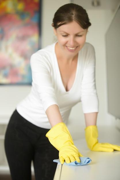 Portret van een jonge lachende vrouw met rubberen handschoenen schoonmaken Gratis Foto