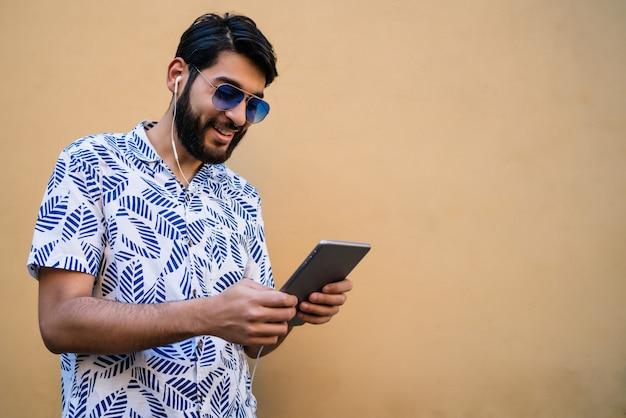 Portret van een jonge latijns-man met behulp van zijn digitale tablet met koptelefoon tegen gele muur Gratis Foto