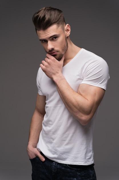 Portret van een jonge man geïsoleerd op een grijze achtergrond. een jonge man met een baard. een man in een t-shirt. mannelijk portret op een grijze achtergrond. stijlvolle mensen. atleet. mannelijk geschiktheidsmodel. Premium Foto