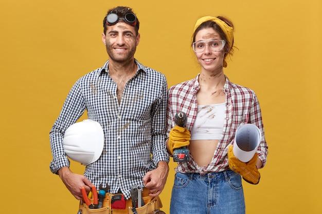 Portret van een jonge man in shirt en broek met riem gevuld met gereedschap en veiligheidshelm staande in de buurt van haar vrouw die hem helpt om dingen te repareren met boormachine en blauwdruk dragen van shirt en spijkerbroek Gratis Foto