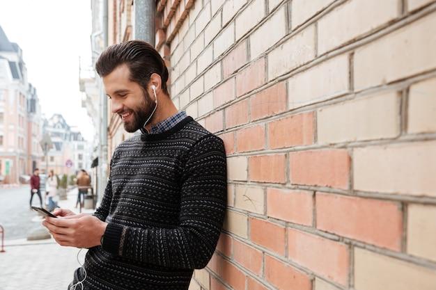 Portret van een jonge man in trui luisteren naar muziek Gratis Foto