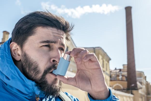 Portret van een jonge man met behulp van astma-inhalator Premium Foto