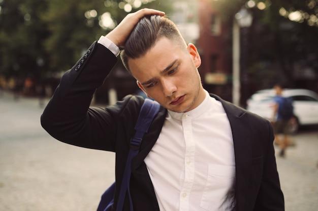 Portret van een jonge man met een rugzak op zijn rug Gratis Foto
