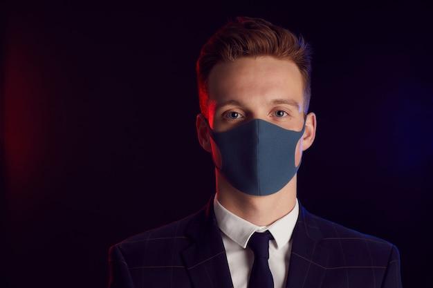 Portret van een jonge man met gezichtsmasker en camera kijken terwijl poseren op feestje staande tegen zwarte achtergrond, kopieer ruimte Premium Foto