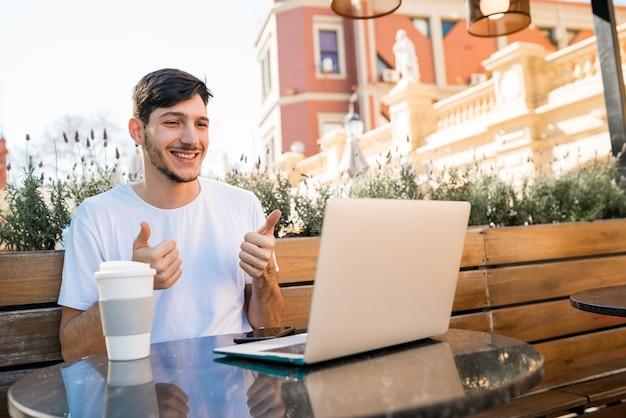 Portret van een jonge man met laptop skype videochat bij coffeeshop. skype en technologie concept. Gratis Foto