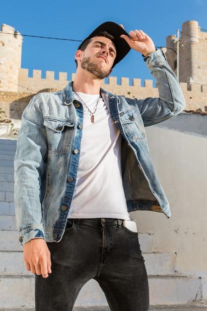 Portret van een jonge man met pet en een denim jasje Premium Foto