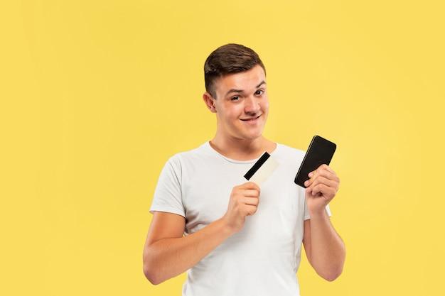 Portret van een jonge man met smartphone en creditcard geïsoleerd op gele muur Gratis Foto