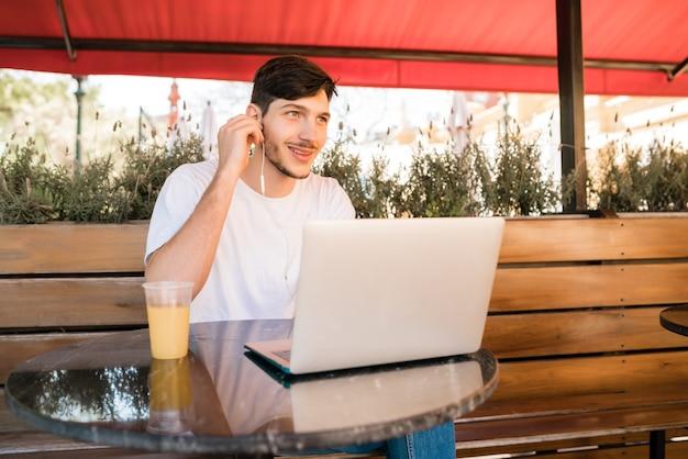 Portret van een jonge man met zijn laptop zittend in een coffeeshop. technologie en levensstijlconcept. Gratis Foto