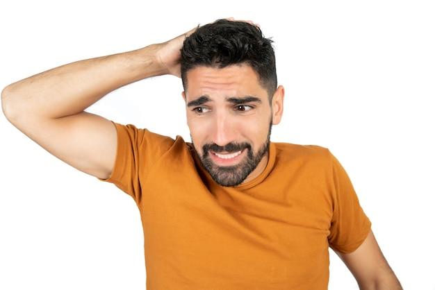 Portret van een jonge man op zoek bezorgd over iets tegen witte ruimte Gratis Foto
