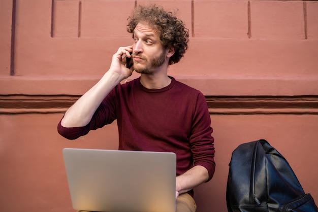Portret van een jonge man praten aan de telefoon en zijn laptop gebruikt terwijl hij buiten zit. technologie en levensstijlconcept. Premium Foto