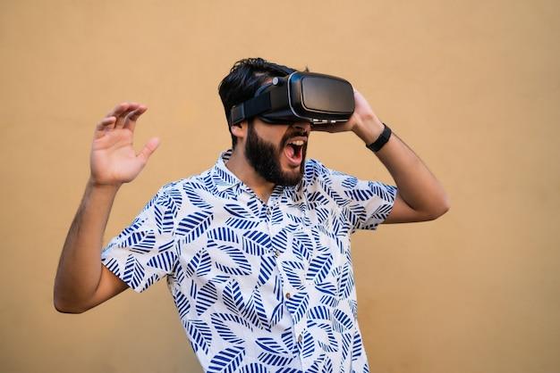 Portret van een jonge man spelen met vr-headset bril van virtual reality tegen gele ruimte. vr-headset bril apparaat. technologie concept. Gratis Foto
