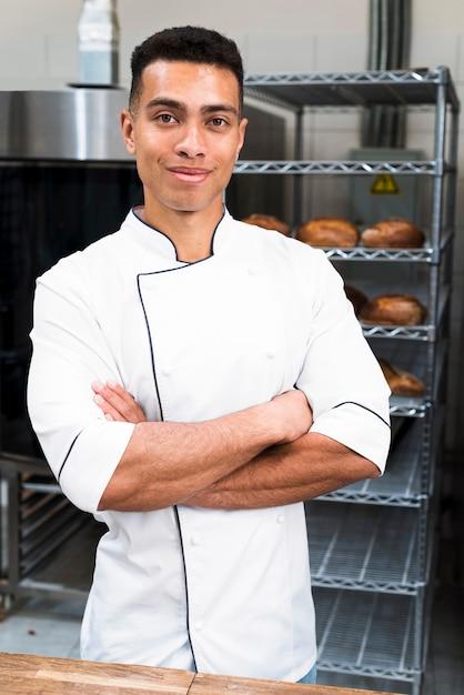 Portret van een jonge mannelijke bakker met zijn gekruiste wapens het bekijken camera Gratis Foto