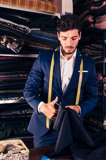 Portret van een jonge mannelijke kleermaker die in zijn workshop werkt Gratis Foto