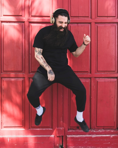 Portret van een jonge mens die in lucht met hoofdtelefoon op zijn oor tegen rode deur springt Gratis Foto