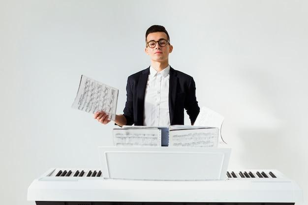 Portret van een jonge mens die muzikaal blad houdt dat zich achter de piano tegen witte achtergrond bevindt Gratis Foto