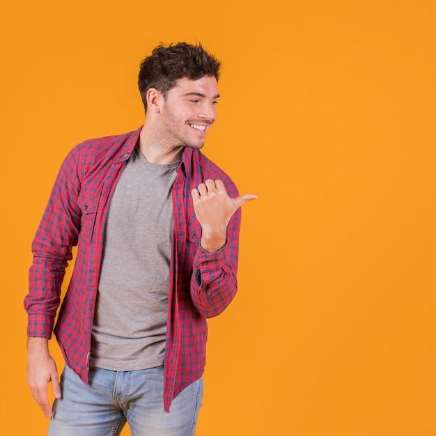 Portret van een jonge mens die zijn duim toont aan kant tegen een oranje achtergrond Gratis Foto