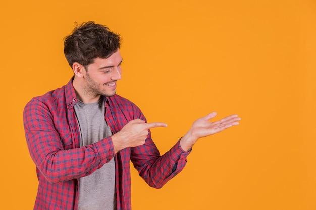 Portret van een jonge mens die zijn vinger op hand tegen een oranje achtergrond richt Gratis Foto