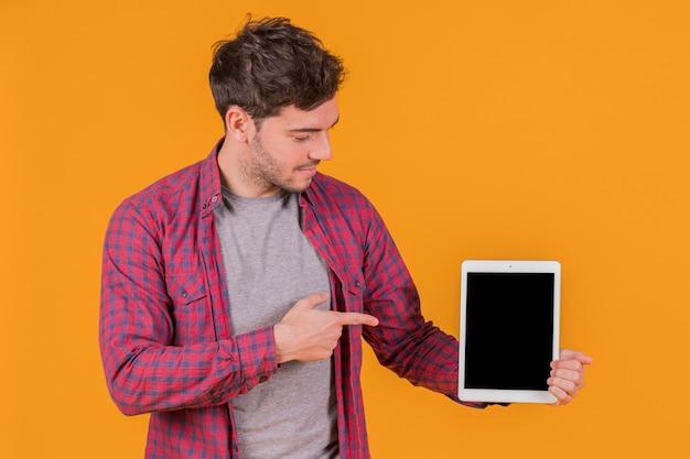 Portret van een jonge mens die zijn vinger richt op digitale tablet tegen een oranje achtergrond Gratis Foto