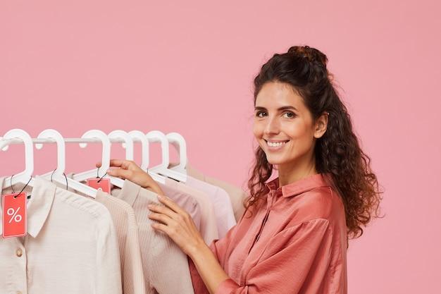 Portret van een jonge modeontwerper glimlachend in de camera terwijl je in de buurt van het rek met kleren staat Premium Foto