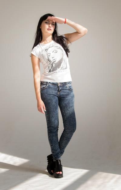 Portret van een jonge mooie brunette vrouw in een wit t-shirt en spijkerbroek Premium Foto