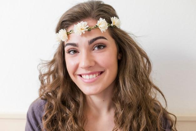 Portret van een jonge mooie vrouw die een bloemenkroon draagt. ze lacht binnenshuis. lifestyle. horizontale weergave Premium Foto