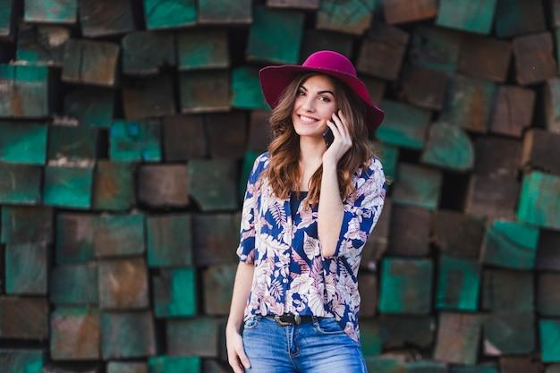 Portret van een jonge mooie vrouw die vrijetijdskleding en een moderne hoed draagt en op haar mobiele telefoon spreekt. zij bevindt zich over groene houtsnedenachtergrond en glimlacht. buitenshuis levensstijl. Premium Foto
