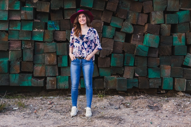 Portret van een jonge mooie vrouw die vrijetijdskleding en een moderne hoed draagt, zich over groene houtsneden bevindt en glimlacht. buitenshuis levensstijl. Premium Foto