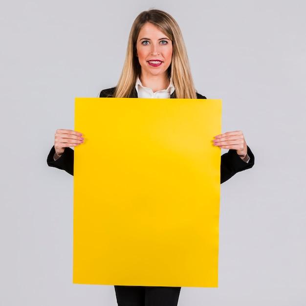 Portret van een jonge onderneemster die het lege gele aanplakbiljet op grijze achtergrond toont Gratis Foto