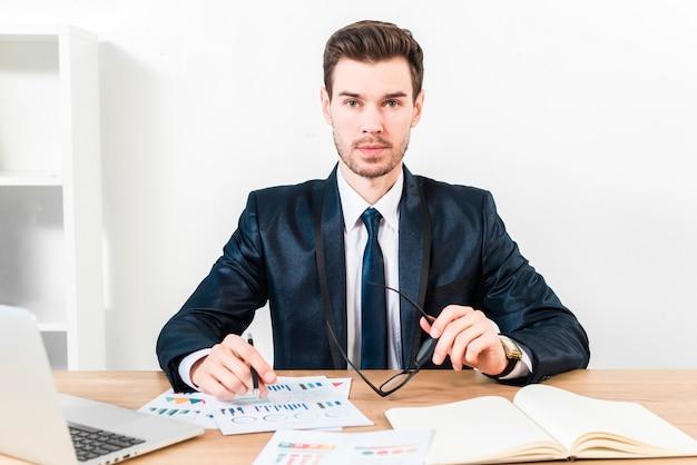 Portret van een jonge pen van de zakenmanholding over de grafiek en oogglazen die in hand aan camera kijken Gratis Foto