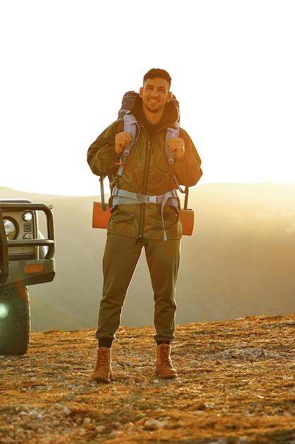Portret van een jonge reizigersmens in wandeluitrusting die zich dichtbij zijn off-road auto bevindt Premium Foto