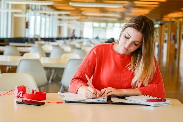 Portret van een jonge student die studeert aan de universiteitsbibliotheek. onderwijs en levensstijl concept. Gratis Foto