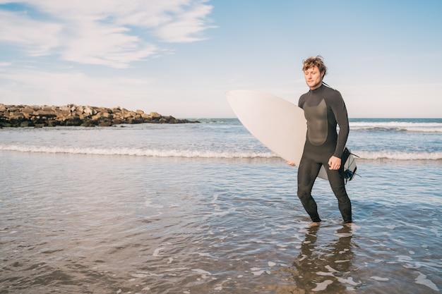 Portret van een jonge surfer die het water verlaat met een surfplank onder zijn arm. sport en watersport concept. Gratis Foto