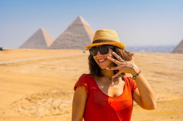 Portret van een jonge toerist in rode jurk die geniet van de piramides van gizeh, het oudste grafmonument ter wereld. in de stad caïro, egypte Premium Foto