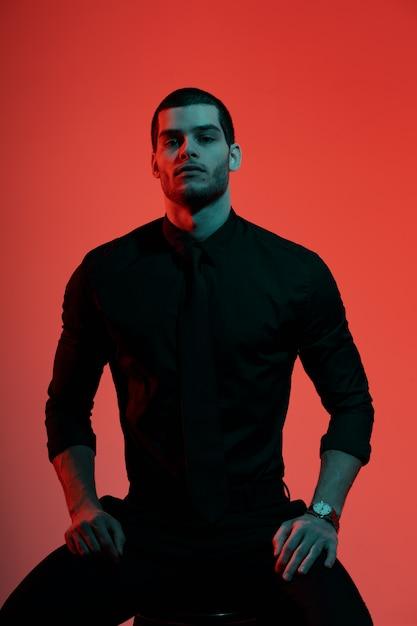 Portret van een jonge vertrouwen knappe zakenman in blauw en rood licht Gratis Foto