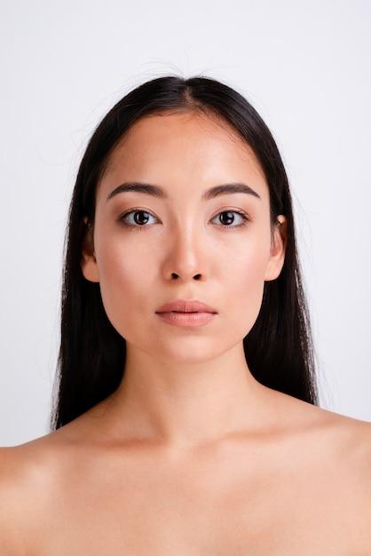 Portret van een jonge vrouw die de camera bekijkt Gratis Foto