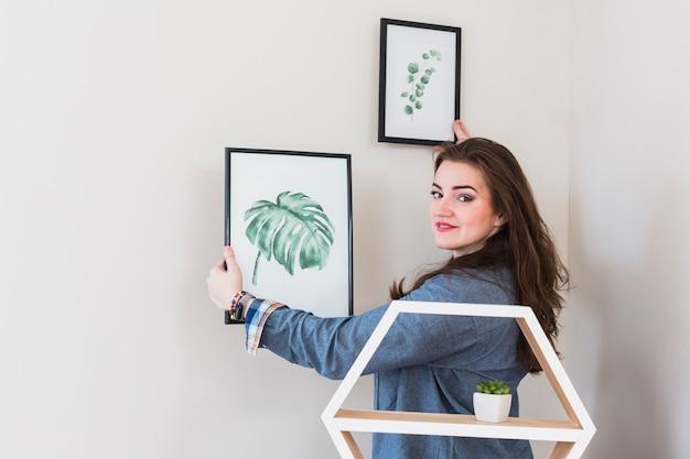 Portret van een jonge vrouw die de omlijsting op muur bevestigt die aan camera kijkt Gratis Foto