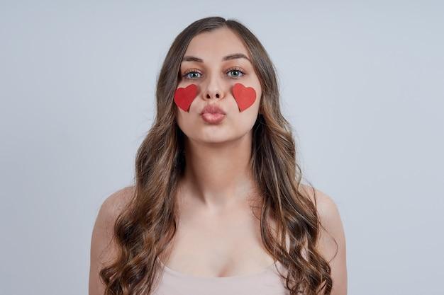 Portret van een jonge vrouw die een kus blaast met rode harten die aan haar wangen worden geplakt. fijne valentijnsdag. Premium Foto