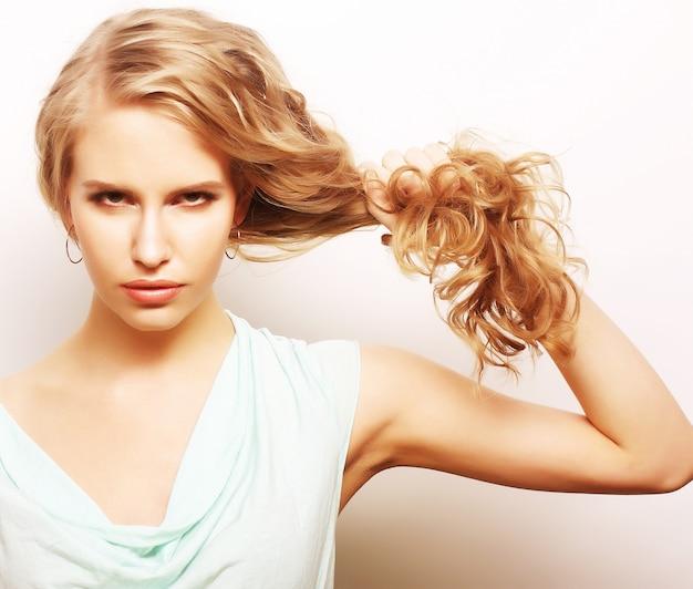 Portret van een jonge vrouw die haar lang gezond krullend haar houdt Premium Foto