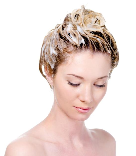 Portret van een jonge vrouw die met het inzepen hoofd neerkijkt - geïsoleerd op wit Gratis Foto