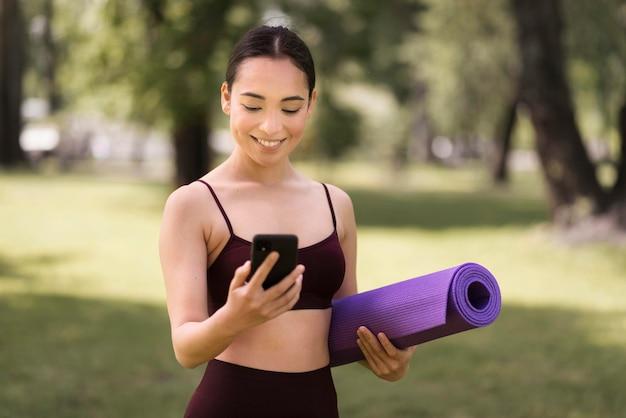 Portret van een jonge vrouw die mobiele telefoon controleert Gratis Foto