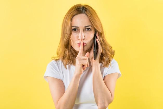 Portret van een jonge vrouw die op mobiele telefoon spreekt die vinger plaatst over lippen die aan camera kijken Gratis Foto