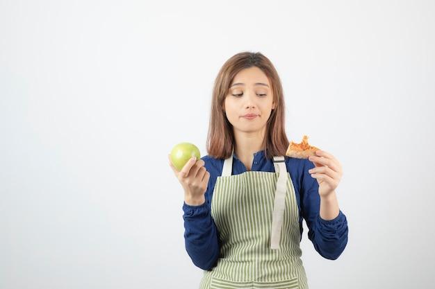Portret van een jonge vrouw die plak van pizza en appel over witte muur bekijkt. Gratis Foto