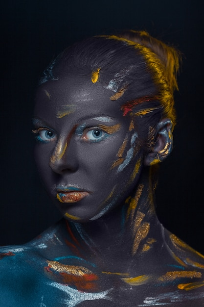 Portret van een jonge vrouw die poseren bedekt met zwarte verf Gratis Foto